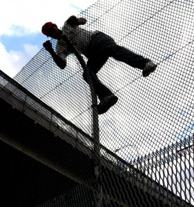 An illegal immigrant trying to climb over a security fence that divides the Mexico-United States' border